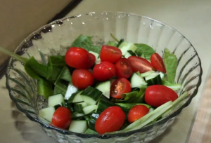 mixing cherry tomatoes with the salad