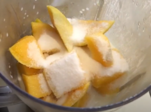 mixing yogurt milk mixture with mangoes with additional sugar